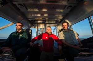 Joe Boucher (helm) Jonathan Moore(standing) and Ryan Harris (side scan sonar operator seat) in RV Investigator. Photo by Thierry Boyer